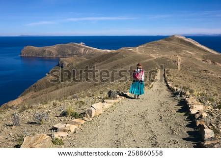 ISLA DEL SOL, LAKE TITICACA, BOLIVIA - NOVEMBER 7, 2014: Unidentified woman in traditional wear walking on path on November 7, 2014 on Isla del Sol (Island of the Sun), Lake Titicaca, Bolivia - stock photo
