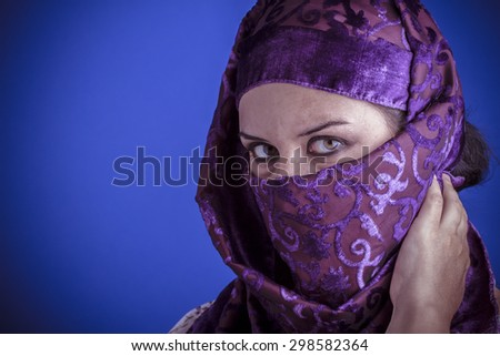 Islam, Beautiful arabic woman with traditional veil on her face, intense look - stock photo