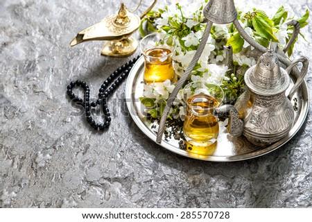 Islamic holidays decoration. Ramadan kareem. Tea glasses and pot, arabian lantern and rosary. Oriental hospitality concept. - stock photo