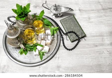 Islamic holidays decoration. Ramadan kareem. Tea table setting, arabian lantern, holy book quran and rosary. Oriental hospitality concept. - stock photo