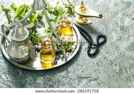 Islamic holidays decoration. Ramadan kareem. Tea tableware, arabian lantern and rosary. Oriental hospitality concept. Retro style toned photo - stock photo