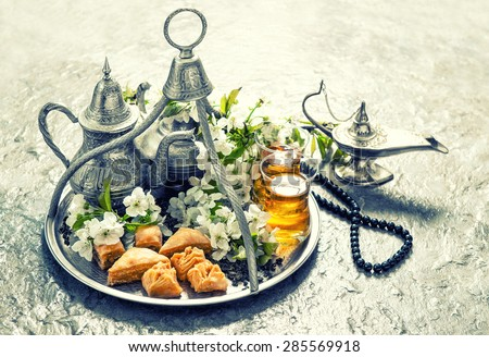 Islamic holidays food with decoration. Ramadan kareem. Eid mubarak. Oriental hospitality concept. Tea glasses and pot, traditional delight baklava. Vintage style toned picture - stock photo