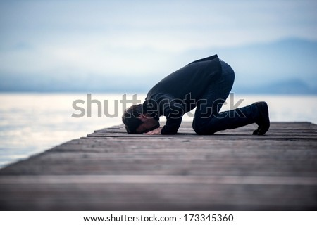 Islamic man praying on a wooden pier in dusk - stock photo