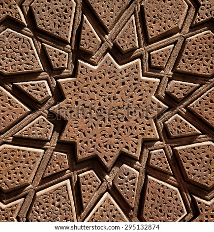 Islamic Persian design consisting stars and flowers, carved on the surface of an old wooden door. - stock photo