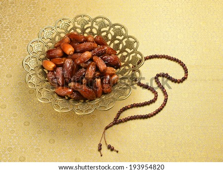 Islamic rosary and ornate bowl of dates - stock photo