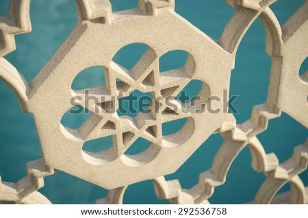 Islamic star pattern architectural detail on fence in front of bright blue water background - stock photo