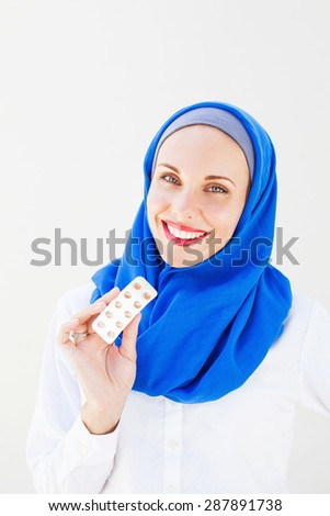 islamic woman holding pills - stock photo