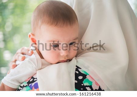 Islamic woman hugging her cute little baby - stock photo