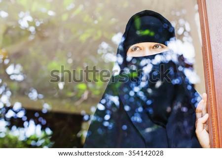 islamic woman looking at the window closeup - stock photo