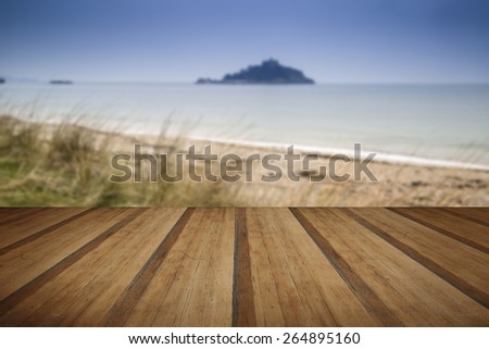 Island castle landscape viewed through sand dunes with wooden planks floor - stock photo