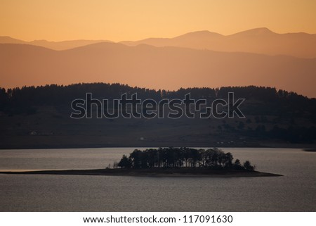 island in bulgarian batak dam lake- autumn dusk time - stock photo