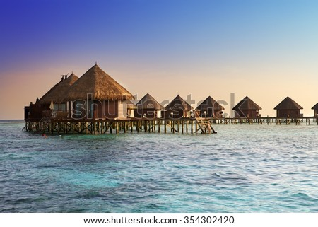 Island in ocean, over water villas at the time sunset. - stock photo