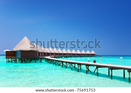 Island in ocean, overwater villas - stock photo