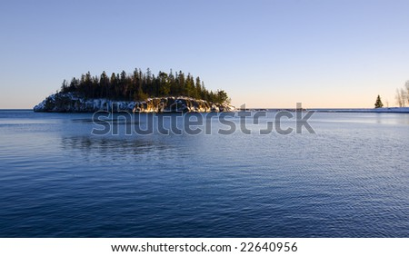 Island in the cold blue water of the north shore of Lake Superior in Minnesota - stock photo