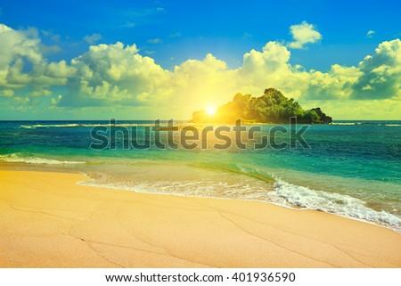 Island in the ocean and beautiful sunrise - stock photo