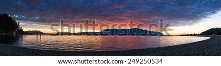 Island Panorama. Panoramic view of Orcas Island, in the Puget Sound area of western Washington, is enveloped in a fiery sunset seen along Legoe Bay on the shores of Lummi Island. - stock photo