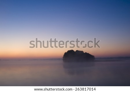 Island silhouette on calm foggy lake water surface just before sunrise, Mazury, Poland - stock photo