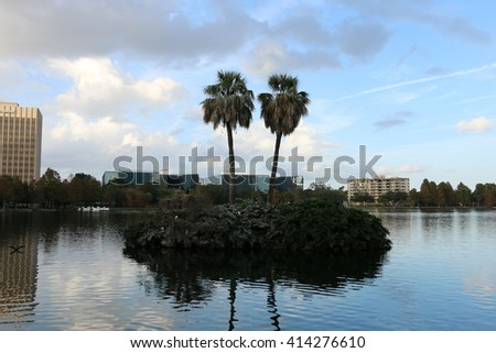 Island with two palm trees on the lake in the city center/A small island with two palm trees/Please visit my portfolio for more photos like this! - stock photo