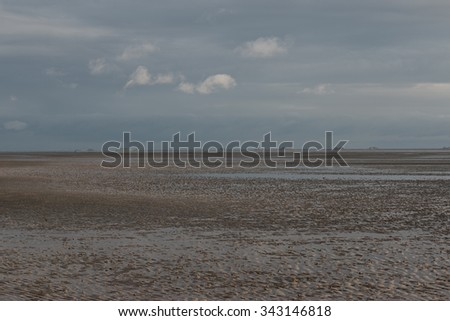 islands on the horizon low tide foreground storm blue sky - stock photo