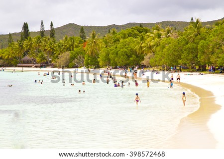 isle of pines ,life on beach,vacation,holiday,people on the beach,green water,holiday beach,boat on beach,trees near beach,isle beach,island,dream island,isle of pines,new caledonia ,wonderful island  - stock photo