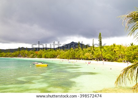 isle of pines ,life on beach,vacation,holiday,people on the beach,green water,holiday beach,boat on beach,trees near beach ,isle beach,island,dream island,isle of pines,new caledonia ,wonderful island - stock photo