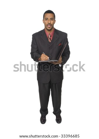 Isloated full length studio shot of an African American man looking at the camera while smiling and writing on his notepad.