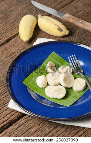 isolate bunch of ripe cultivated banana on blue plate - stock photo