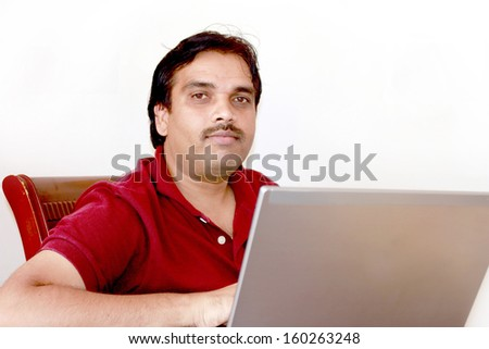 Isolate image of an Indian middle age successful happy man with Laptop and this represents a concept of working from home, online sales, operating online business, checking data , mails in internet