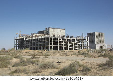 Isolate island of stalled or unfinished housing construction project in the Arabian desert with unfinished tower block waiting for resumption of building works showing corroded steel reinforcing