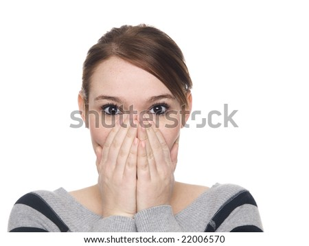 Isolate studio shot of a casually dressed young adult woman covering her mouth in surprise with eyes wide.