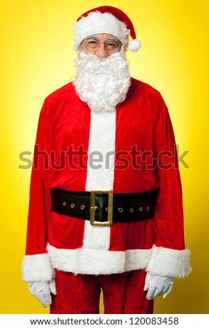 Isolated aged male dresses in Santa attire against yellow background. - stock photo