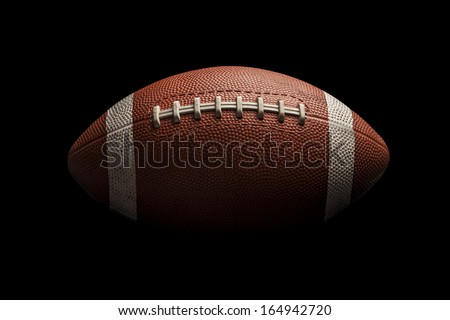 Isolated American football ball on high contrast black background - stock photo