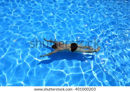 isolated azure water pool and swimmer in the water