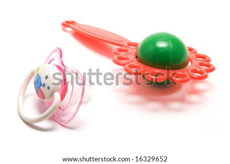 isolated baby's dummy and rattle
