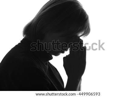isolated black and white portrait of a woman with her hands folded near the bridge of the nose due to despair