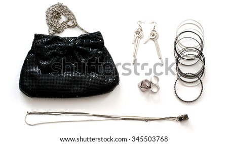 Isolated black clutch bag with accessories in rock style over white - stock photo