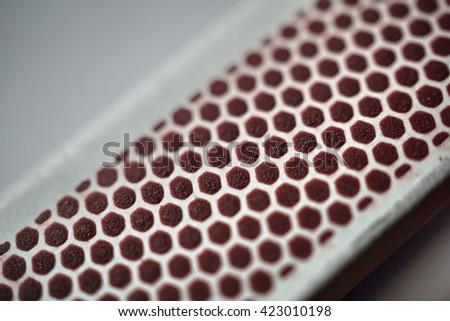 Isolated box of safety matches with its black striking surface with the honeycomb shapes on the narrower side
