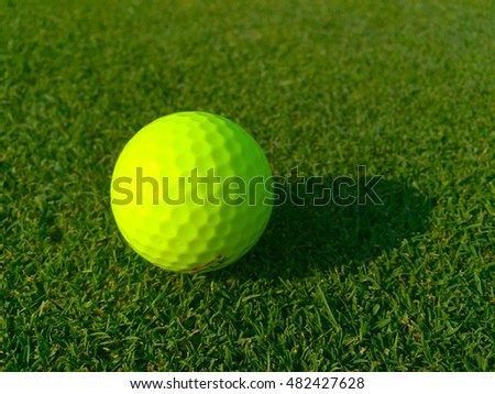 Isolated bright green golf ball site on golf course grass waiting for player to putt into hole for par score. Morning sunrise shadow cast on fairway. Low Angle