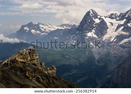 isolated building on a cliff in the Alps overlooking a deep valley and tall snowy mountains in the background  - stock photo