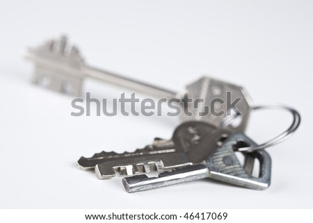 Isolated bunch of four various metal keys over white