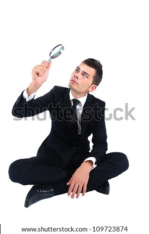 Isolated business man with magnifying glass - stock photo