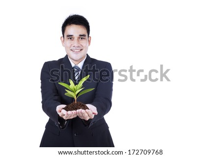 Isolated businessman holding a green plant in his hands - stock photo