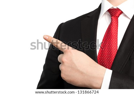 Isolated businessman in a suit and red tie points the finger at an object - stock photo