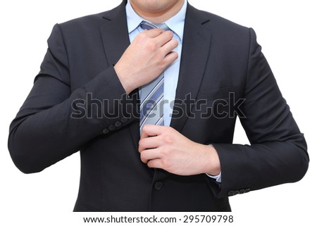 isolated businessman in suit tying the necktie - stock photo