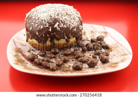 Isolated chocolate donut and chocolate balls with cocoa powder on a plate  - stock photo