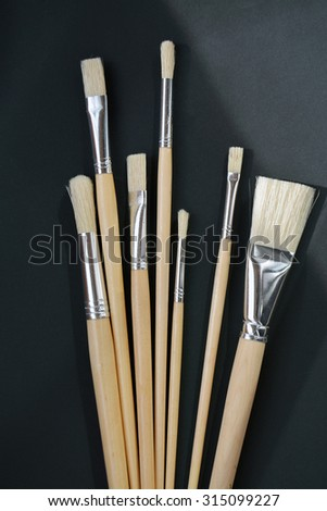 Isolated clean brushes with wooden handle on black background