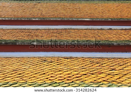 isolated close-up fragment of multi colored tiled roof in the sunlight