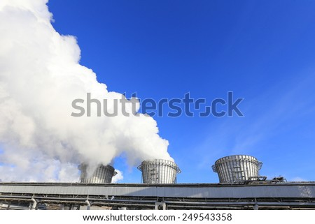 isolated close-up of white smoke from the chimney of the plant against the blue sky - stock photo