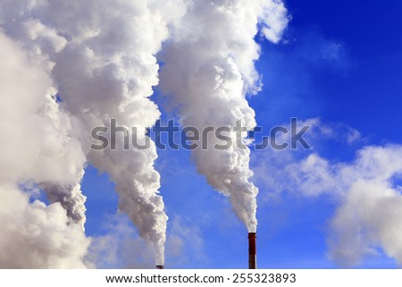 isolated close-up of white smoke from the chimney of the plant against the blue sky