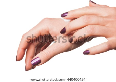 Isolated close up on female hands in relaxed gesture with purple fingernail polish applying moisturizing lotion over white background - stock photo